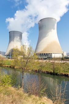 Schoorstenen van nucleaire fabriek en rivier in de zomer