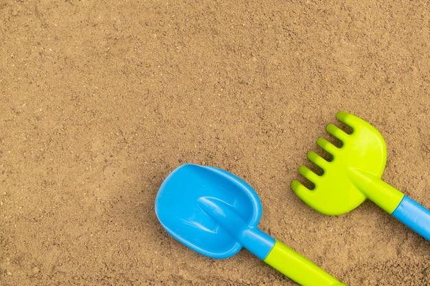 Schop en hark in zandbak. zandspeelgoed voor buiten voor kinderen. zomer concept. met plaats voor tekst.