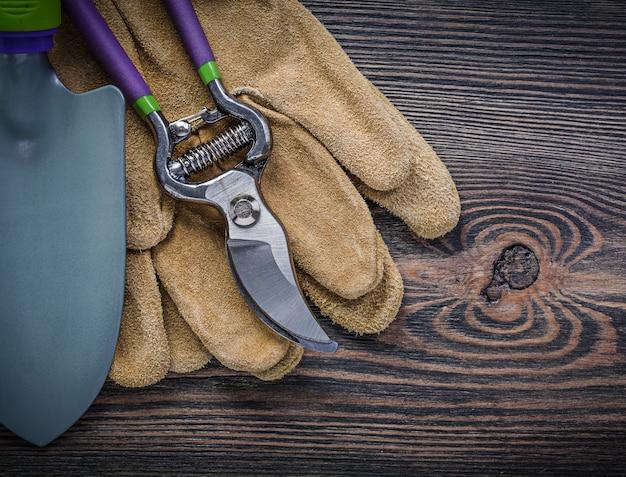 Schop snoeischaar beschermende handschoenen op een houten bord