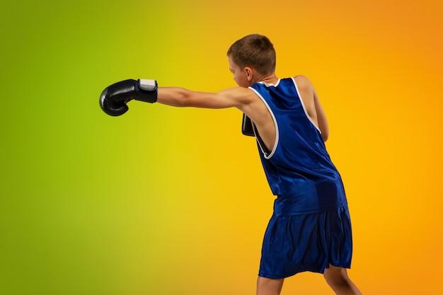 Schoppen. tiener professionele bokser training in actie, beweging geïsoleerd op verloop achtergrond in neonlicht. schoppen, boksen. concept van sport, beweging, energie en dynamische, gezonde levensstijl.