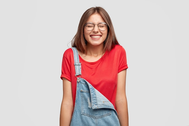Schot van aangenaam uitziende gelukkig meisje lacht positief, loenst gezicht, giechelt van grappige grap