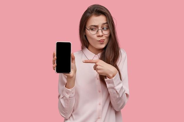 Schot van aantrekkelijke donkerharige vrouw houdt moderne mobiele telefoon in de hand met mock-up scherm, adverteert nieuwe gadget van haar favoriete bedrijf