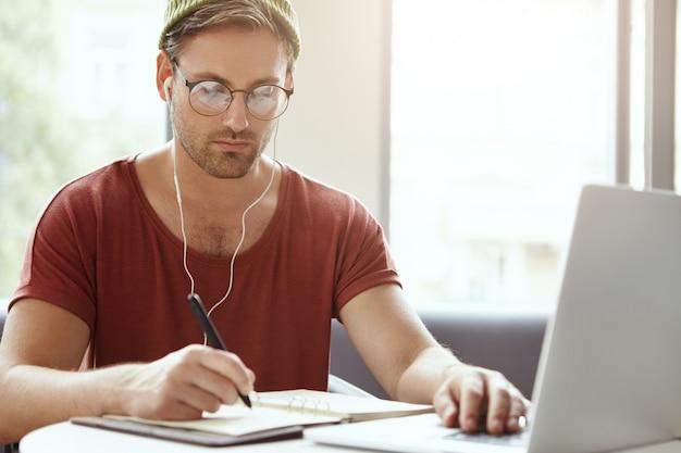 Schot van aantrekkelijke gerichte man in casual kleding, schrijft in notitieblok noodzakelijke informatie