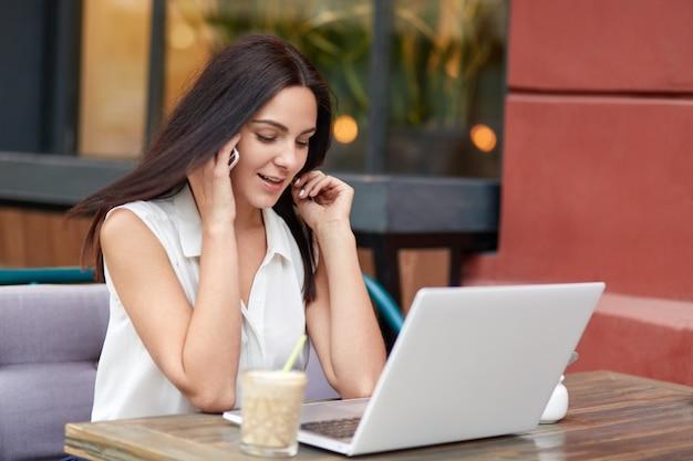 Schot van aantrekkelijke vrouw met donker lang haar, spreekt met zakenpartner op mobiel, gebruikt laptop voor surfen op internet en afstandsbanen, drinkt cocktail, poseert in gezellig buitencafé