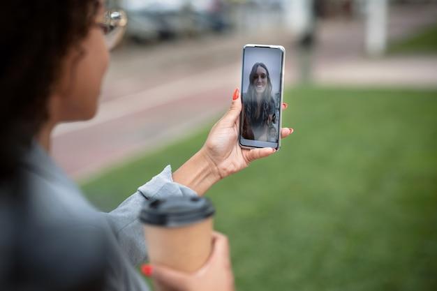 Schot van achteraanzicht van een vrouw die een videogesprek voert met een mooie jonge zakenvrouw terwijl ze koffie op straat houdt.