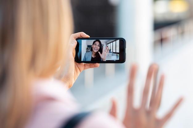Schot van achteraanzicht van een vrouw die een videogesprek voert met een mooie jonge zakenvrouw terwijl ze op straat blijft.