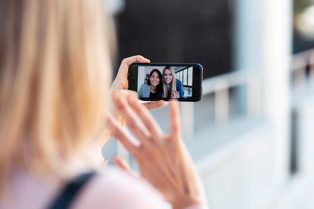 Schot van achteraanzicht van een vrouw die een videogesprek voert met twee mooie jonge zakenvrouwen terwijl ze op straat blijft.