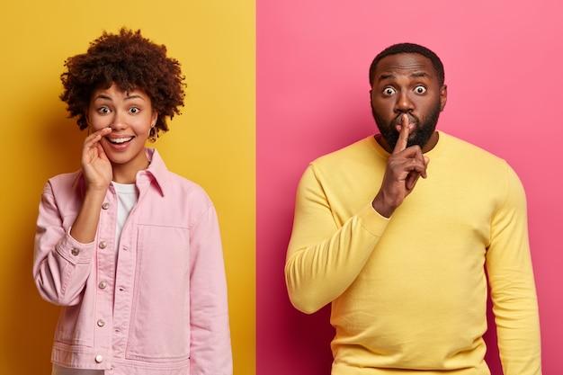 Schot van afro-amerikaanse dame giechelt positief over grappige grap, verbaasde bebaarde man maakt stilte gebaar, vertelt geheime informatie
