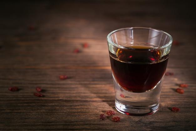 Schot van alcoholische drank op donkere rustieke houten achtergrond. kruidenbitterlikeur met verschillende natuurlijke ingrediënten. detailopname