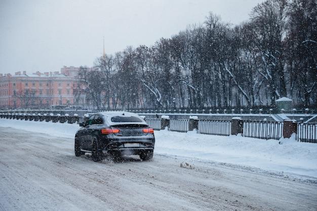 Schot van auto bedekt met witte sneeuw, rijdt langzaam als weg in glad en bedekt met dikke witte sneeuw