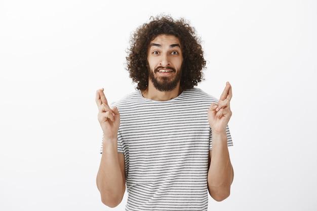Schot van bezorgd knappe bebaarde oost-mannelijk model met afro kapsel in gestreept t-shirt, gekruiste vingers opheffen en hopen, wens doen en geloof smeken om het te vervullen