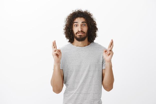 Schot van bezorgd verbijsterd aantrekkelijke bebaarde spaanse man met afro kapsel, vingers kruisen, zenuwachtig wachtend op resultaten