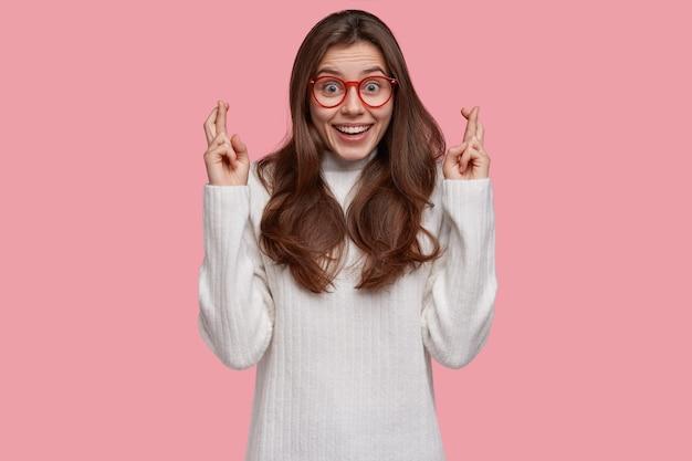Schot van bijgelovige tienermeisje heeft opgewonden blije blik, kruist vingers voor geluk, geloof in iets positiefs
