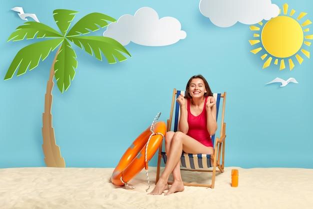 Schot van blij vrouwelijke vakantieganger in rode bikini, balde vuisten, geniet van recreatietijd, vormt op de strandstoel