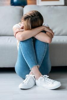Schot van depressieve jonge vrouw die aan haar problemen denkt terwijl ze thuis op de vloer in de woonkamer zit.