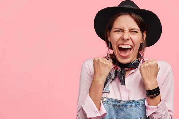 Schot van dolblij jong vrouwtje heeft brede glimlach, heft vuisten met succes op, draagt hoed, heeft positieve uitdrukking, staat tegen roze muur
