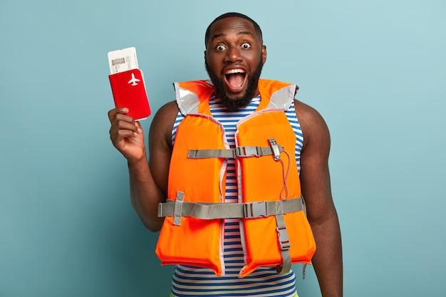 Schot van dolgelukkig donkere man met dikke haren, blij dat hij binnenkort een avontuurlijke reis heeft, houdt paspoort met kaartjes vast