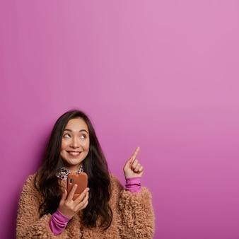 Schot van dromerige jonge vrouw met brede glimlach, donker haar, heeft interessant idee, beveelt iets op lege ruimte aan, maakt gebruik van mobiele telefoon