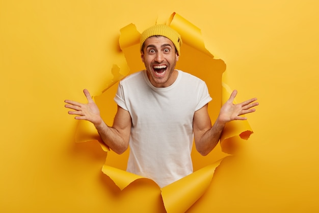 Schot van een gelukkige man draagt een gele hoed en een wit t-shirt, spreidt de handpalmen zijwaarts, blij om een oude vriend te ontmoeten, lacht en kijkt met vreugde