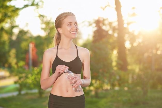 Schot van een jonge mooie vrouwelijke atleet in sportkleding glimlachen op zoek weg met een fles water rust na het uitoefenen van copyspace geluk vitaliteit schoonheid actieve gezonde levensstijl.