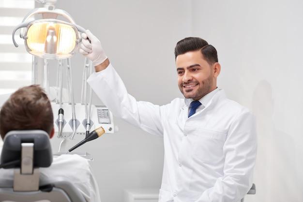 Schot van een mannelijke tandarts lamp vóór tandheelkundig onderzoek van de tanden van zijn patiënt aan te passen copyspace professionaliteit vriendelijke ervaren geneeskunde gezondheidszorg tandheelkunde.