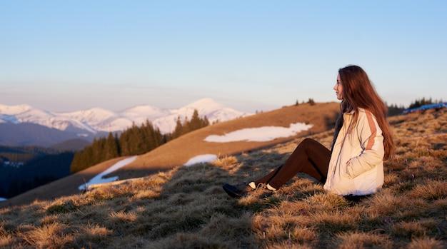 Schot van een vrouw die prachtig uitzicht zittend op de top van een berg bewonderen