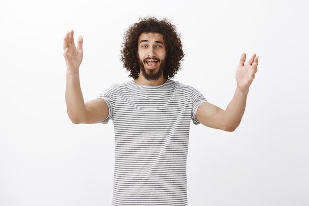 Schot van emotionele knappe spaanse broer met krullend kapsel en baard, handpalmen opheffend en schreeuwend, bekende persoon zien en aandacht trekken