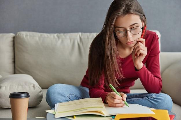 Schot van ernstige geschoolde student met pen in de hand, schrijft curriculum vitae