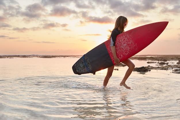 Schot van ervaren surftrainer draagt surfplank, rijdt golven op de oceaan, gaat aan de oever van water, bereidt zich voor op wedstrijd