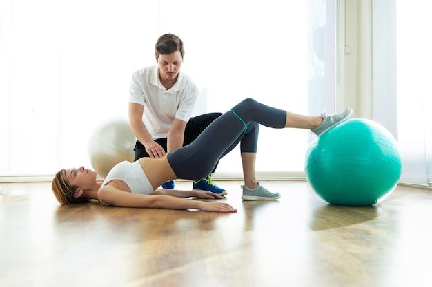 Schot van fysiotherapeut die de patiënt helpt om te oefenen op een fitnessbal in de fysiokamer.