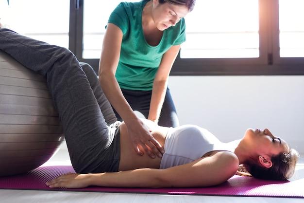 Schot van fysiotherapeut die een mooie zwangere vrouw helpt voor het doen van pilates-oefeningen met bal die zich voorbereidt op de bevalling.
