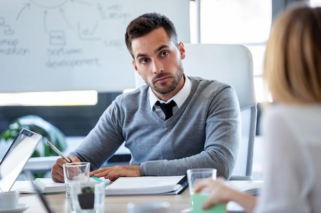 Schot van geconcentreerde jonge zakenman die zijn partner luistert en aantekeningen maakt over coworking-ruimte.
