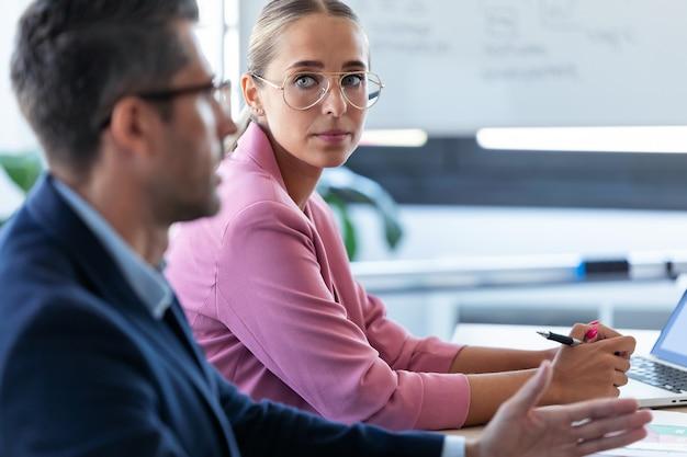 Schot van geconcentreerde jonge zakenvrouw die naar haar partner kijkt en luistert op coworking-ruimte.