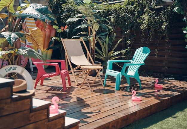 Schot van gekleurde stoelen op de houten vloer tussen de groene planten