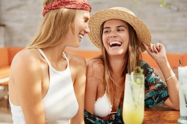 Schot van gelukkig vrouw draagt modieuze zomer hoed en blouse besteedt zitten in café met verse cocktail