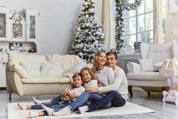 Schot van gelukkige jonge lachende familie zittend op de vloer met hun twee kinderen en genieten van ontspannen thuis.