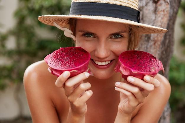 Schot van gelukkige jonge vrouw in hoed houdt dragon fruit