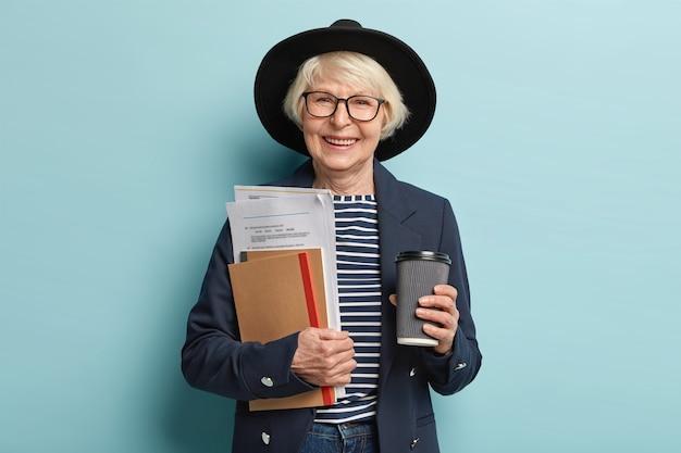 Schot van gelukkige senior ervaren zakenvrouw houdt papieren en portemonnee, drinkt afhaalmaaltijden koffie, blij om succesvol contract te ondertekenen, draagt stijlvolle hoed en jas, vormt binnen. drukke oude werker