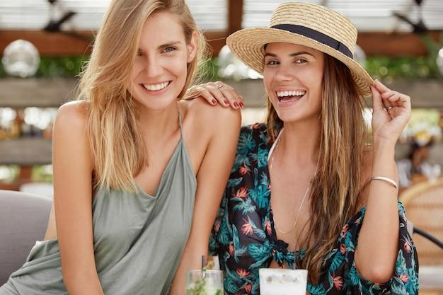 Schot van gelukkige vrouwelijke lesbiennes recreëren samen in coffeeshop, genieten van frisse zomerdrankjes, een brede glimlach, genieten van saamhorigheid. mooie glimlachende mooie jonge vrouw in strooien hoed zit in de buurt van vriend