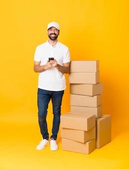 Schot van gemiddelde lengte van leveringsmens onder dozen over geïsoleerde gele muur die een bericht met mobiel verzenden