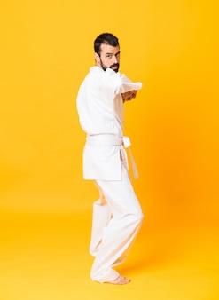 Schot van gemiddelde lengte van mandoing karate over geïsoleerde gele muur