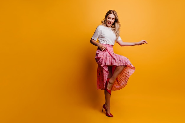 Schot van gemiddelde lengte van mooi slank meisje in lange rok. fascinerende vrouw die op gele muur danst.