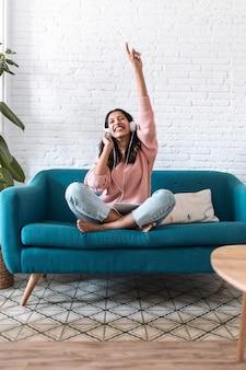 Schot van gemotiveerde jonge vrouw die naar muziek luistert met een digitale tablet terwijl ze thuis op de bank zit.