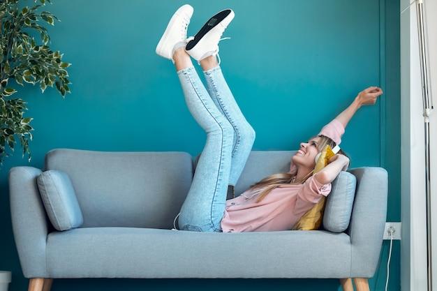 Schot van gemotiveerde jonge vrouw die naar muziek luistert met smartphone terwijl ze thuis op de bank ligt.