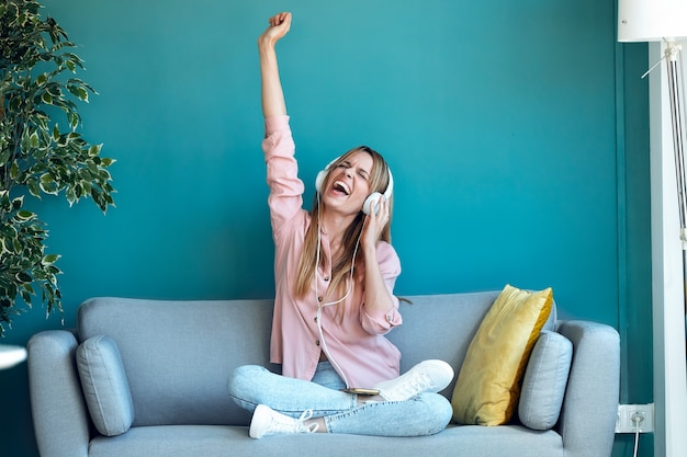 Schot van gemotiveerde jonge vrouw die naar muziek luistert met smartphone terwijl ze thuis op de bank zit.