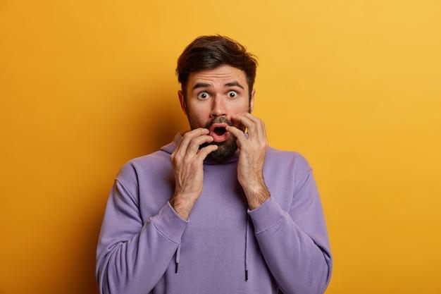 Schot van geschokte bange man die in paniek is, houdt zijn handen dicht bij geopende mond, ziet iets vreselijks, voelt zich opgewonden, draagt paars sweatshirt, geïsoleerd op gele muur, hoort vreselijk nieuws