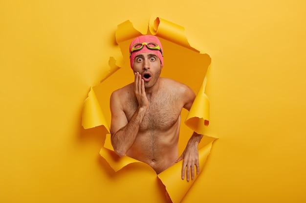 Schot van geschokte jongeman staat topless, als professionele zwemmer, merkt iets ongelooflijks op, draagt een bril en zwembroek