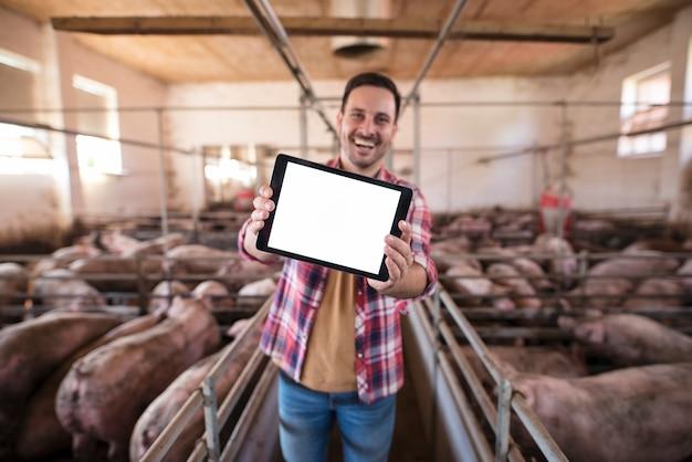 Schot van glimlachende landbouwer die zich in varkenshok bevindt en tabletcomputer onder ogen ziet naar de camera