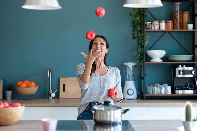 Schot van grappige jonge vrouw jongleren met drie rode appels in de keuken thuis.