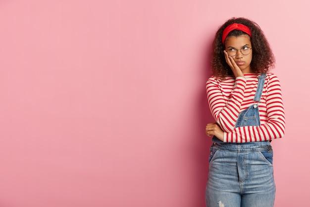 Schot van het sombere ongelukkige tienermeisje poseren in overall met krullend haar